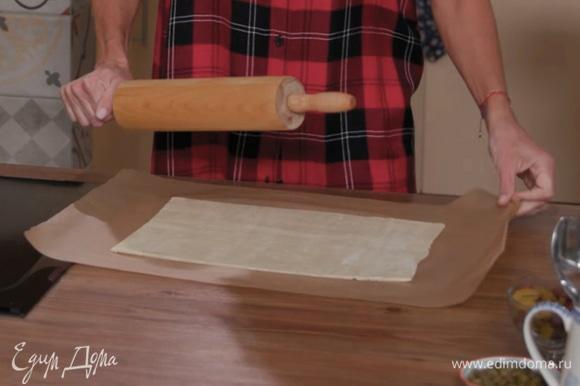 Слоеное тесто выложить на бумагу для выпечки, раскатать.