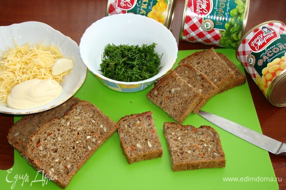 Теперь займемся зеленой «полянкой» для наших поросят. Для этого ломтики хлеба разрезать пополам. Сыр натереть на мелкой терке, к нему добавить зубчик чеснока, пропущенного через пресс, 3 ст. л. майонеза и перемешать. Зелень укропа мелко нашинковать. Хлеб можно взять любой по вкусу. У меня хлеб злаковый, потому что мне кажется, что такая основа-полянка будет еще вкуснее.
