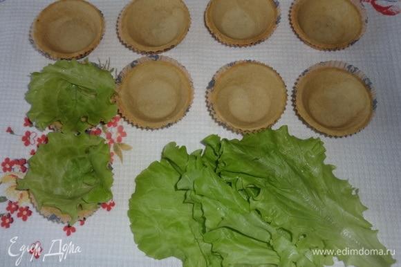 Подготовить тарталетки. Для этого листья салата вымыть, обсушить. Разделить каждый лист вдоль жилки пополам и выложить по кругу в тарталетку. Наполнить корзиночки салатом. Сверху украсить отложенными фасолью, зеленым луком и томатами.