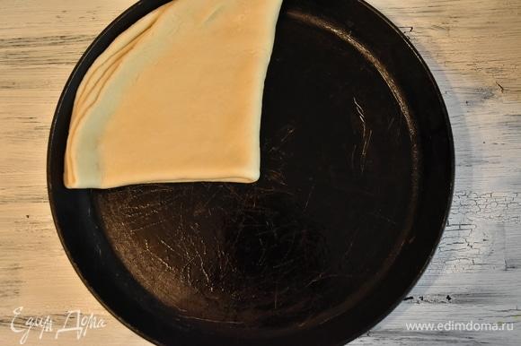 Чтобы тесто легче было перенести на сковороду, складываю его пополам и потом еще раз пополам. Переношу на сковороду, смазанную растительным маслом. Верх получившегося треугольника из теста укладываю в центр и разворачиваю тесто, придавая первоначальную форму.