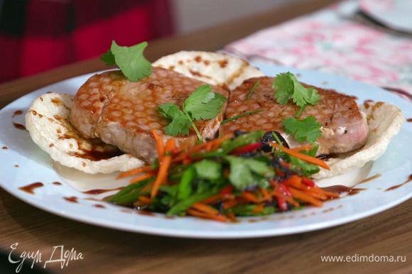Выложить на блюдо пшеничные хлебцы, на них — рыбу. Сверху стейки смазать карамельно-соевым соусом и украсить свежей кинзой, рядом — выложить овощной салат.