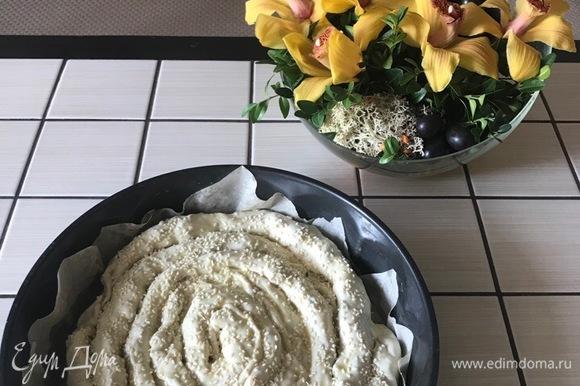 Выкладываем в форму для выпечки в форме улитки. Смазываем яйцом и посыпаем кунжутом. Ставим в духовой шкаф на 40 минут при температуре 180°C.