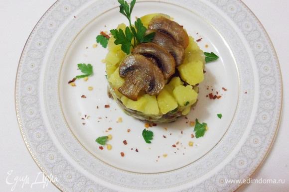 Выложить салат через кулинарное кольцо, украсить ломтиками грибов и зеленью.