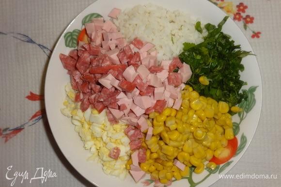 В глубокой миске соединить рис, кукурузу, колбасу, яйца, зелень, перемешать.