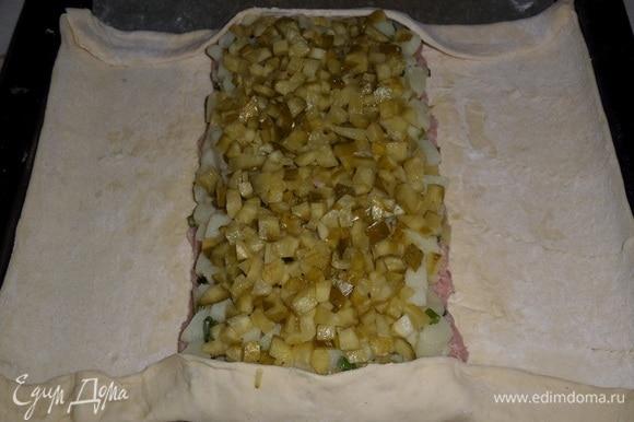 Поверх картофеля выкладываем нарезанные маринованные огурцы, равномерно распределяем. Подгибаем края пласта теста сверху и снизу.