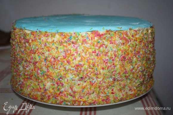 Далее украшаем бока торта цветной кокосовой стружкой. Сверху укладываем круг из мастики голубого цвета.