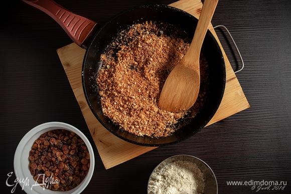За это время приготовим начинки. Растопите все сливочное масло. Заранее разогрейте духовку до 190°C. Белую булку нарежьте на кубики. Положите в духовку и приготовьте крутоны. Измельчите крутоны в блендере в крошку. На сковороду вылейте три столовые ложки растопленного масла и поджарьте на нем крошки. Перемешайте с миндальной мукой. Хрустящий слой готов.