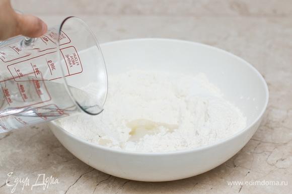 В широкой миске смешайте все ингредиенты для теста. Мука у всех разная, поэтому наливайте воду постепенно, а при необходимости добавьте еще немного муки/воды, чтобы тесто приобрело нужную консистенцию.