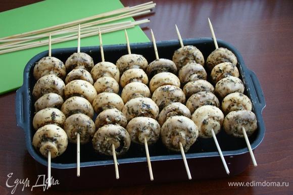 Маринованные грибочки нанизать на шпажки, смоченные водой, примерно штук по 5–6 и уложить на противень с высокими бортиками, создавая имитацию мангала. Запекать в разогретой до 200–210°C духовке минут 20.
