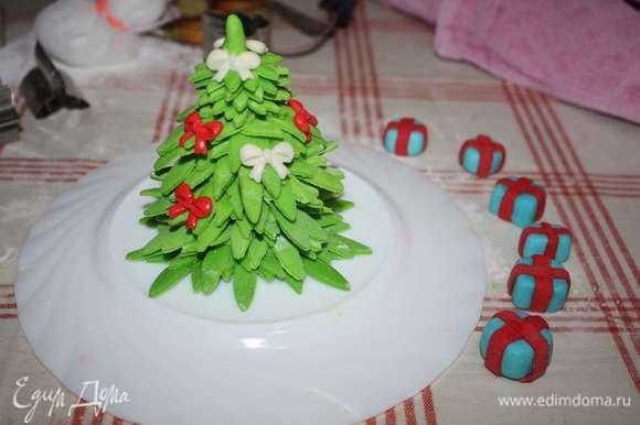 Мастику окрасим пищевыми красителями в желаемые цвета. Сделаем елку, подарки и желаемые фигурки для украшения.