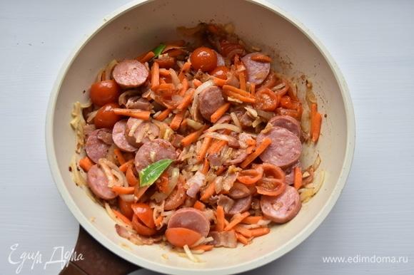 Краковскую колбасу нарезать кружочками и добавить к овощам с беконом. Перемешать, немного обжарить все вместе. Вместо краковской колбасы можно взять охотничьи колбаски.
