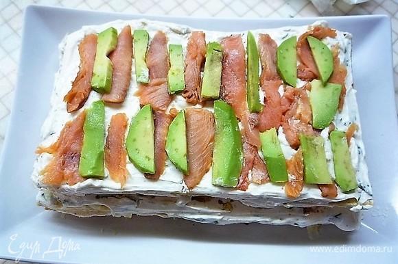 Затем укладываем еще один корж, смазываем кремом, укладываем ломтики рыбы и авокадо.