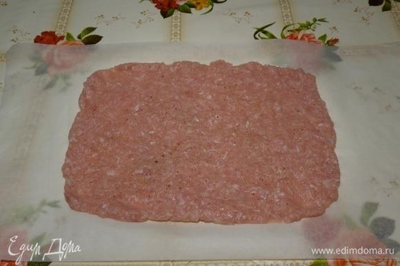 На столе расстилаем пергамент. Выкладываем мясной фарш. Равномерно распределяем в виде прямоугольника. Солим, перчим по вкусу.