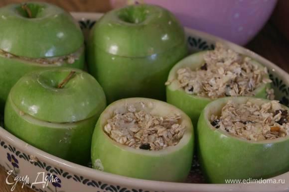 Яблоки поместить в жаропрочную керамическую форму, наполнить выемки овсяной смесью и накрыть крышечками.