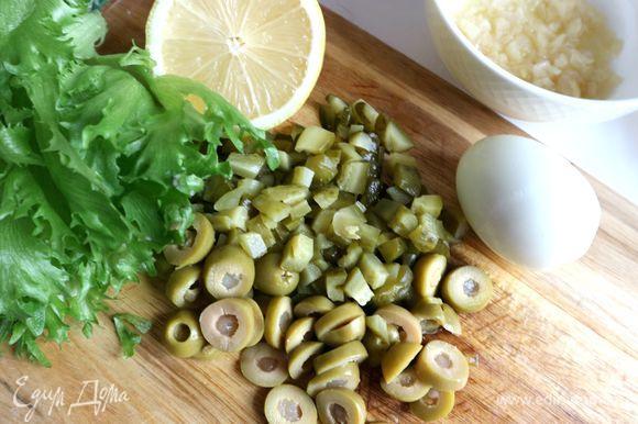 Очистить яйцо, дать ему полностью остыть. Нарезать оливки, фаршированные лимоном, колечками, маринованные огурцы — мелкими кубиками.