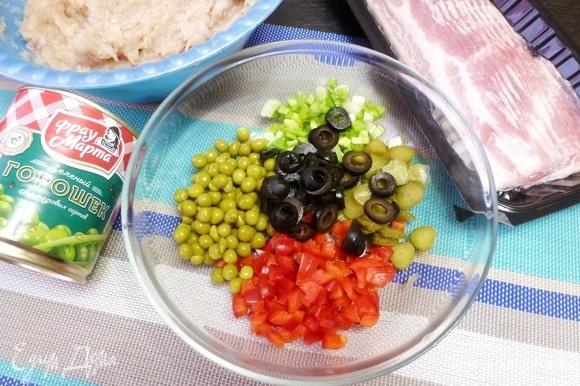 Приготовить наполнитель для террина. С консервированного горошка ТМ «Фрау Марта» слить жидкость. Маслины и маринованные корнишоны нарезать колечками, сладкий перец — мелким кубиком и измельчить зеленый лук.