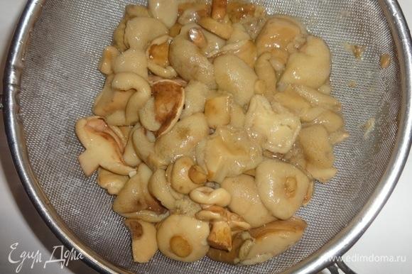 Маринованные грибы откинуть на сито. Также промыть под проточной водой, дать воде стечь. У меня домашние маринованные грибочки, привезенные родственниками из Тамбова. Если попадаются очень крупные кусочки грибов, можно их нарезать помельче.