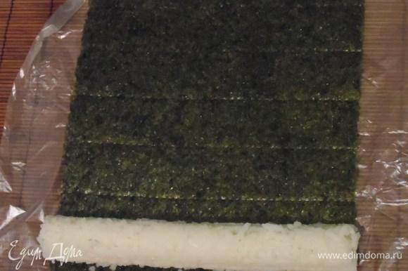 Выложить на рис сыр и огурец. С помощью циновки начать заворачивать ролл.