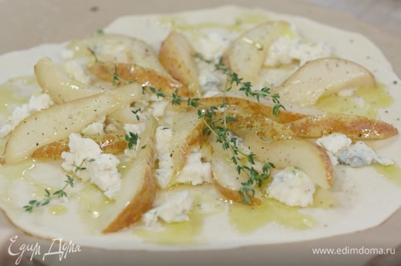 Выложить на тесто кусочки горгонзолы. Сверху — карамелизированную грушу и несколько веточек тимьяна. Еще раз сбрызнуть оливковым маслом и посыпать смесью молотых перцев.