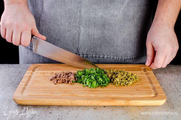 Измельчите кинзу, промойте и мелко нарежьте каперсы, анчоусы достаньте из масла и также измельчите.