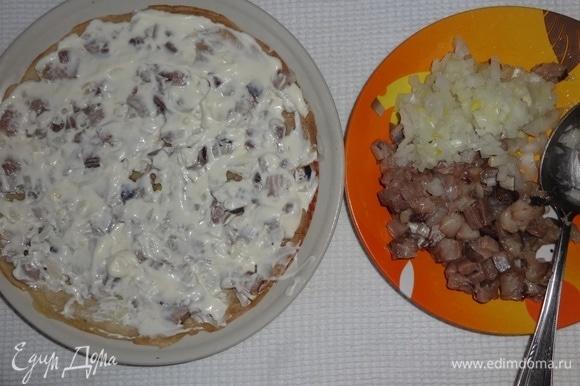 На плоское блюдо выложить блинчик, на него — половину нарезанной сельди и половину лука, смазать 3 ст. л. майонеза.