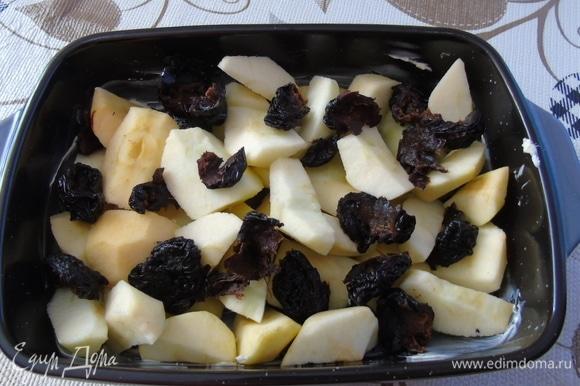 Форму смазать маслом. Яблоки очистить и нарезать кусочками. Сложить в форму вперемешку с кусочками чернослива.