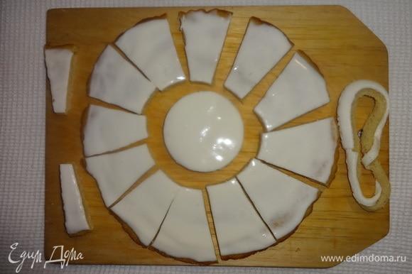 Достать из холодильника светлый корж, смазанный кремом. Крем уже хорошо застыл. С помощью стаканов разного диаметра вырезать посередине коржа круг и тонкое кольцо. Тонкое кольцо убрать. Широкое кольцо разрезать на части (это лепестки «ромашки»). Я вырезала еще 2 узких части, чтобы при выкладывании на крем был виден просвет. Один из лепестков также не понадобился.