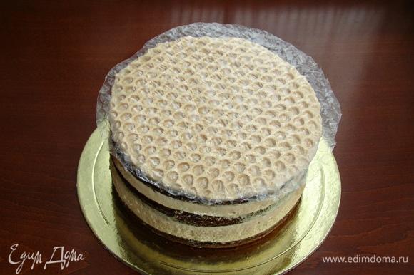 Часть оставленного крема нанести равномерно на верх торта и сверху уложить круг из упаковочной пленки (тщательно промыть и высушить заранее). Пленку слегка вдавить, чтобы в креме проявился рисунок наших сот. Торт снова поставить в холодильник на полчаса.