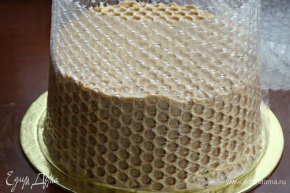 Затем обмазать бока торта оставшимся кремом и обернуть пузырчатой пленкой, слегка вдавливая ее, чтобы образовался красивый рисунок в виде сот. Торт поставить в холодильник на несколько часов.