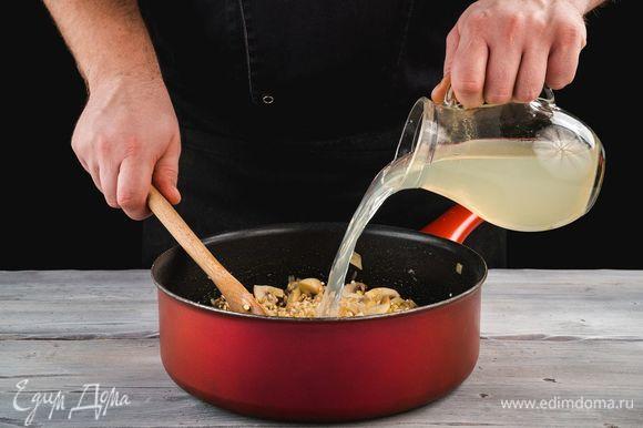 Влейте 200 мл бульона и тушите, постоянно помешивая. Продолжайте доливать бульон порциями, пока перловка не будет полностью готова.