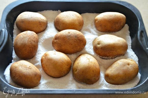 В глубокий противень насыпьте 1 пачку соли, разровняйте. Сверху равномерно распределите картофель.