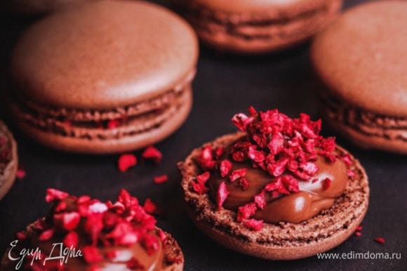 Готовые «крышечки» разделить попарно, на одну половинку нанести шоколадный ганаш, посыпать сублимированной вишней, накрыть второй половинкой, аккуратно прижать.