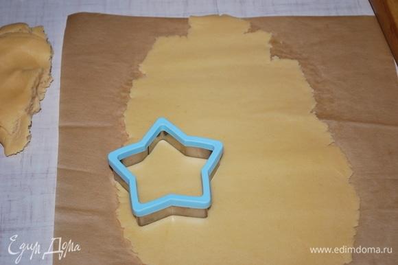 Раскатайте тесто на бумаге для выпечки, формочкой вырежьте фигурки.