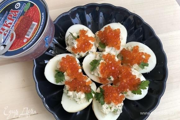 Сверху на яйца выложить красную икру ТМ «Восточный берег» и украсить веточкой петрушки.