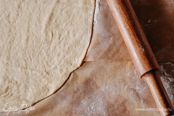 Посыпьте поверхность мукой и тонко раскатайте тесто.