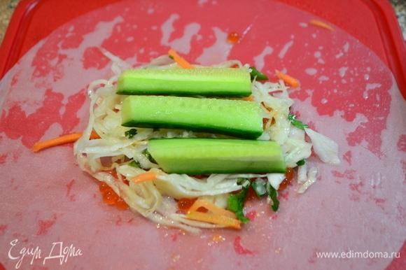 На смоченной в воде рисовой бумаге распределить икру, далее — горсть квашеной капусты с зеленью, дольки огурцов.
