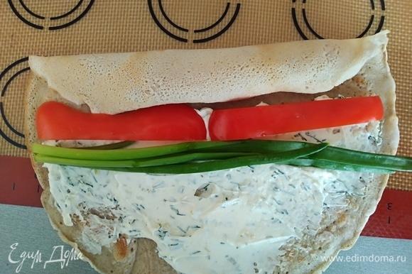 Оставшуюся часть блина намазать сыром. Положить перец и несколько стеблей лука.