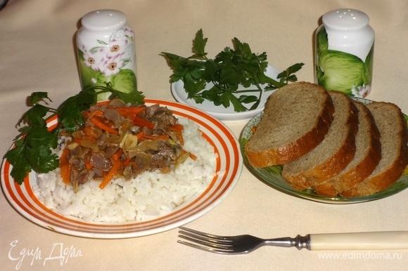 На тарелку выложить порцию риса, сверху положить куриные желудки с овощами, украсить зеленью и подать к столу. Приятного аппетита!
