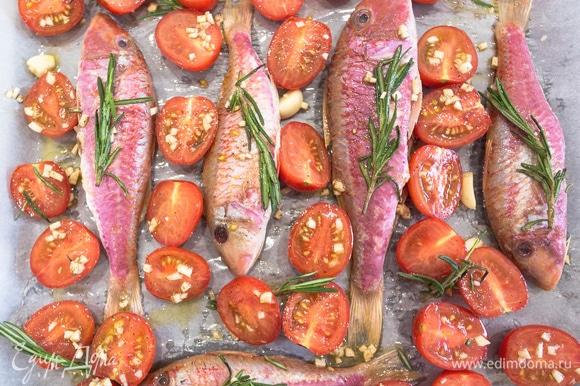 Выкладываем помидоры на противень, сверху поливаем соком от помидоров с чесноком и розмарином. Внутрь барабульки кладем мелко нарезанный чеснок — так она будет еще ароматнее. Запекаем в разогретой до 200°C духовке в течение 20 минут.