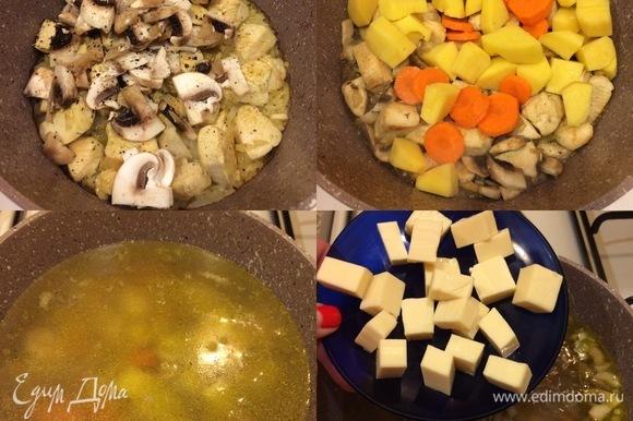 Затем добавить грибы, морковь, картофель, перемешать, накрыть крышкой и потушить 2–3 минуты. Спустя указанное время заливаем бульон, накрываем крышкой и варим суп 15 минут. Плавленый сыр нарезать небольшими кубиками, добавить в суп и, помешивая, довести до кипения. Варить 3–4 минуты.