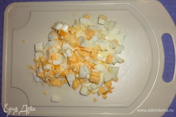 Яйца сварить вкрутую, остудить, почистить. Одно яйцо нарезать на 6 частей, остальные — небольшими кубиками.
