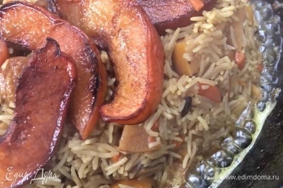 Как только рис достигнет состояния «почти готов» и вода почти вся выпарится, традиционно собираем «горку». Закапываем в нее чеснок. Обложить горку дольками обжаренной айвы.