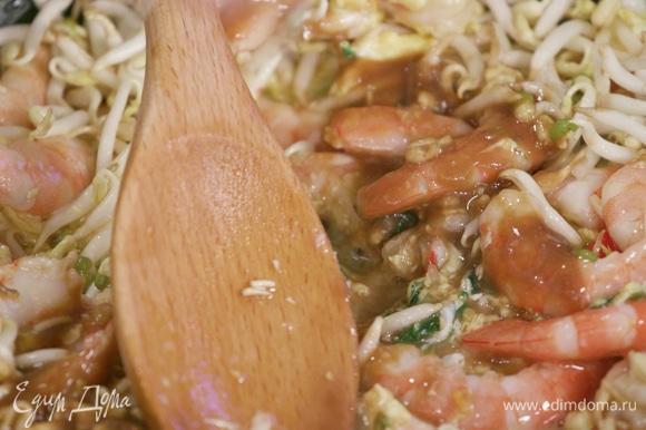 Добавить ростки сои, тамариндовую пасту, рыбный соус, выдавить немного сока лайма и перемешать.