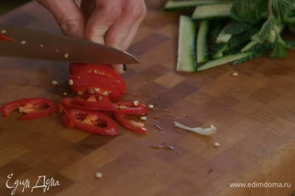 Перец чили вместе с семенами нарезать тонкими колечками.
