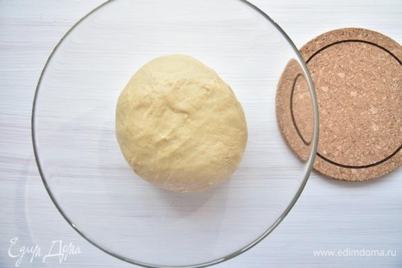 В тесто частями ввести мягкое сливочное масло. Готовое тесто положить в посуду и накрыть пленкой или салфеткой. Оставить на час для подъема.