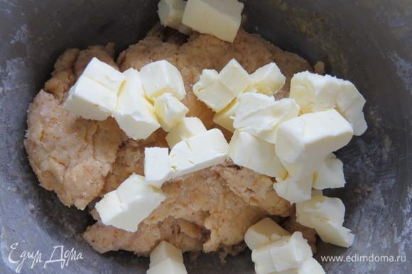 Ввести сливки, перемешивать до тех пор, пока тесто не впитает всю жидкость. Уменьшить обороты миксера и ввести половину сливочного масла.