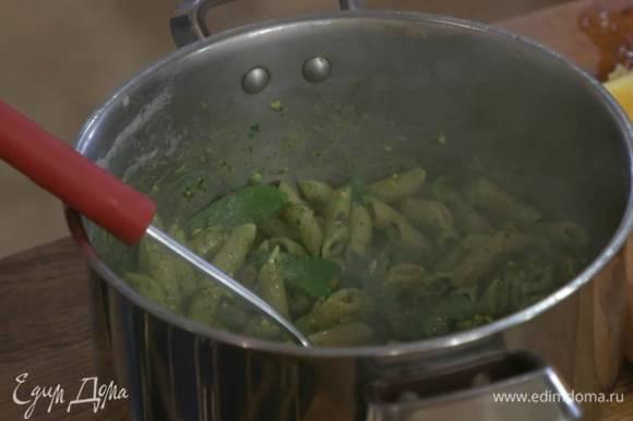 К горячим макаронам с горохом добавить песто и немного воды, в которой варились макароны, все перемешать.