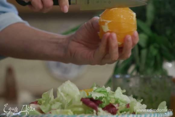 С апельсина срезать кожуру и над салатными листьями вырезать из перепонок мякоть.