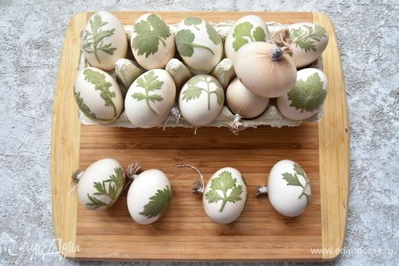 Яйца хорошо помыть под проточной водой. Наложить листочки. Сверху зафиксировать аппликацию капроном, натянуть, концы закрепить с противоположной стороны с помощью нитки.