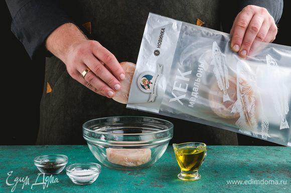 Разморозьте и промойте медальоны хека ТМ «Капитан Вкусов», добавьте соль, перец, оливковое масло.